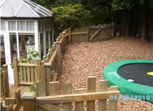 play barked area, sunken trampoline, fencing and gates.